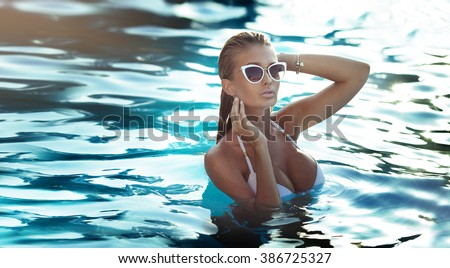 Blonde sexy woman with perfect body posing in fashionable swimsuit, relaxing on pool.