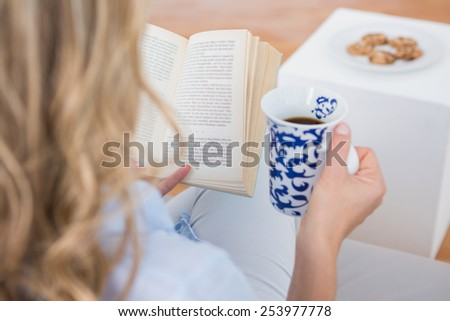 Blonde sitting on couch reading with cup of coffee at home in the living room - stock photo