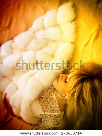 Blonde sleeping sheltered fur blanket - stock photo