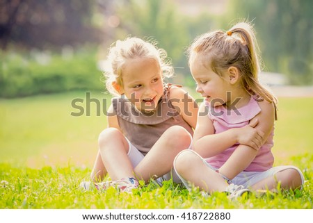 blonde smiling sister play in a garden