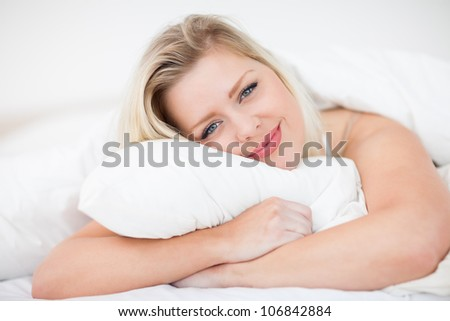 Blonde smiling while embracing a pillow in a bed