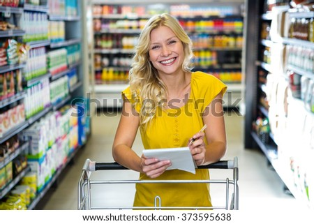 Blonde smiling woman checking list in supermarket - stock photo