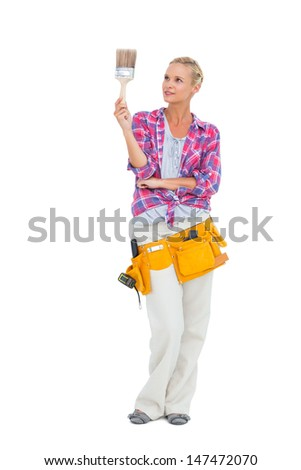 Blonde standing while looking at paint brush on white background - stock photo