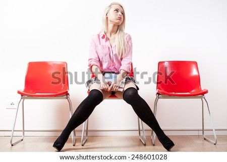 blonde student girl bored in a waiting room with red chairs - stock photo
