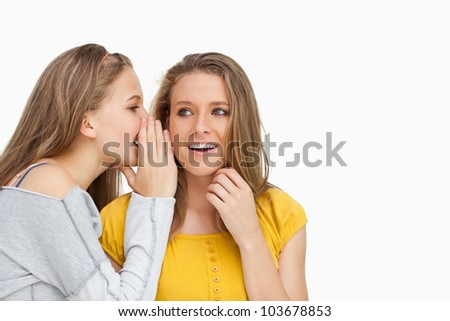 Blonde student whispering to her beautiful friend against white background