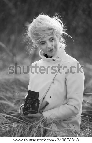 Blonde stylish woman photographer keep retro camera in hands - stock photo