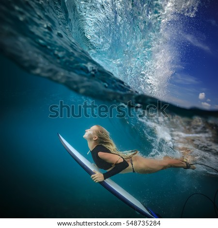 Blonde surfer in bikini with surf board dive under ocean wave lip. Underwater sport activity with fun. Family lifestyle,water sport lessons and beach swimming activity on summer vacation with children