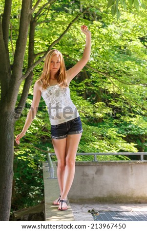 Blonde teen girl walking on a wall - stock photo