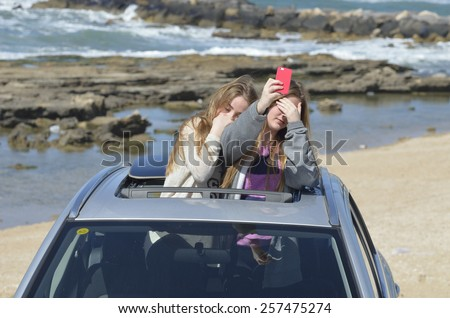 blonde teen girls with smart phone on the background of the sea in the car  sunroof - stock photo