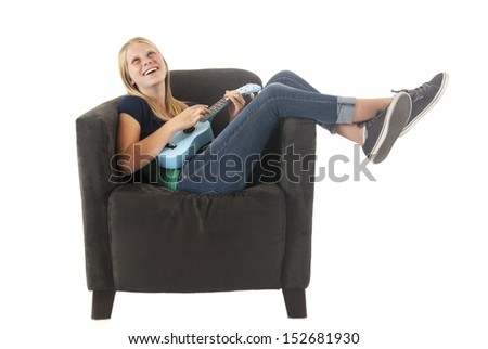 blonde teen playing a ukulele in chair