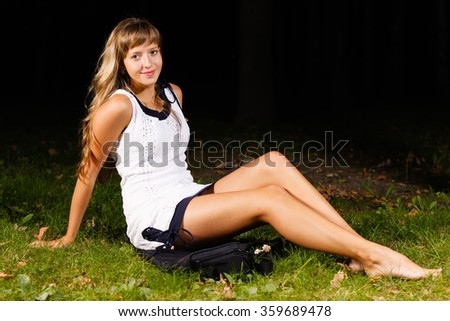 blonde teenage girl lying on the grass - stock photo