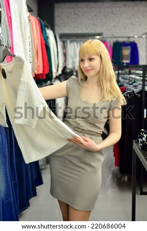Blonde tries a new dress in the shop