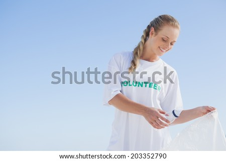 Blonde volunteer picking up trash on the beach on a sunny day - stock photo