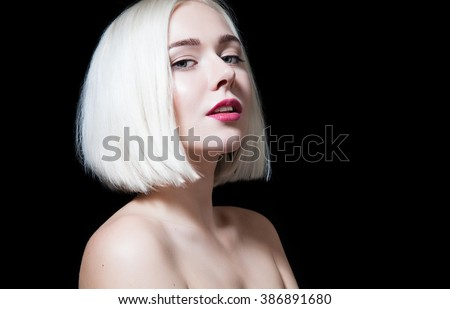 Blonde with shiny short hair and bare shoulders on a black background - stock photo