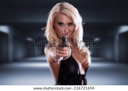 blonde woman aiming with a gun - stock photo