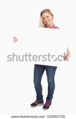 Blonde woman beaming while pointing at a placard against a white background - stock photo