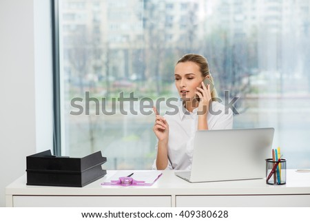Blonde woman behind her desk, working and making phone calls - stock photo