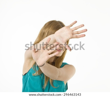 Blonde woman blocking face with hands.