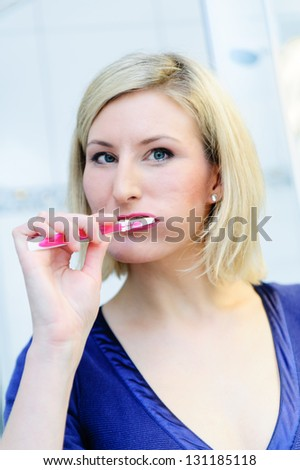 Blonde woman brushing her teeth in the bathroom - stock photo