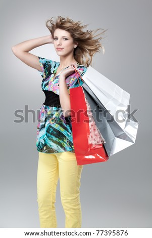 blonde woman carrying shopping bags wind hair