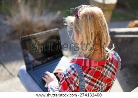 Blonde woman chatting on laptop outdoor, outdoor wi-fi connected laptop - stock photo