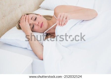 Blonde woman checking her temperature at home in the bedroom - stock photo