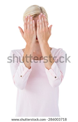 Blonde woman covering her face on white background