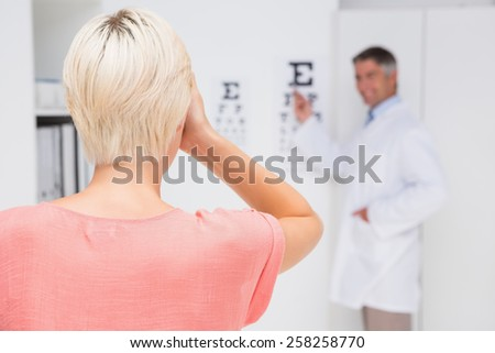 Blonde woman doing eye exam in medical office - stock photo