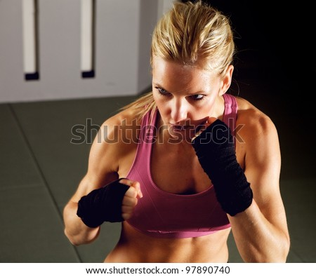 Blonde woman doing martial arts workout in a gym