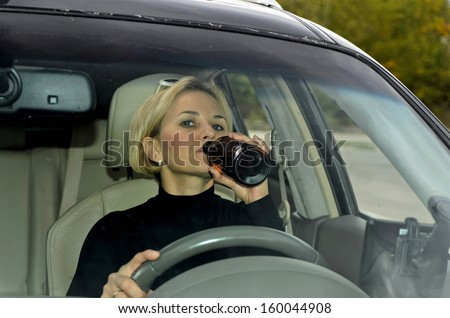 Blonde woman drinking alcohol while driving a car - stock photo