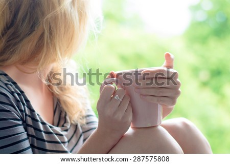 Blonde woman drinking coffee in the garden  - stock photo