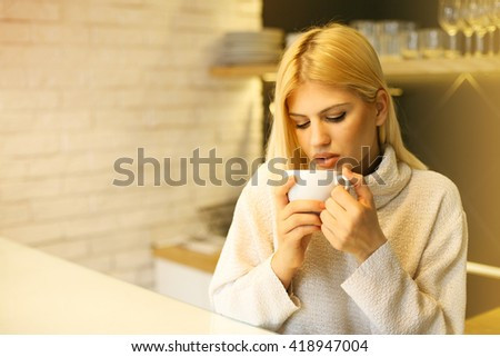 Blonde woman drinking coffee in the morning.  - stock photo