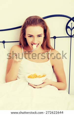 Blonde woman eating breakfast in bed - stock photo