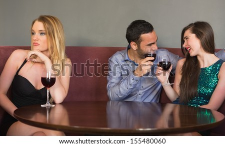 Blonde woman feeling alone as two people are flirting beside her in a nightclub - stock photo