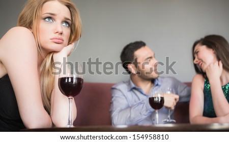 Blonde woman feeling jealous of couple flirting beside her in a bar - stock photo