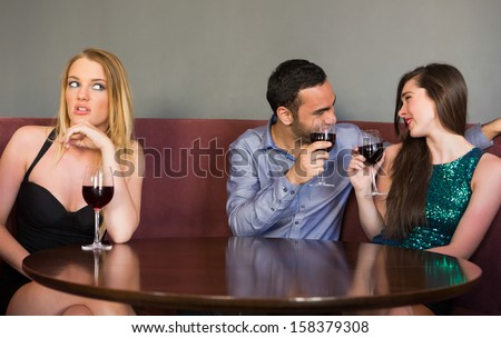 Blonde woman feeling lonely as two people are flirting beside her in a night club - stock photo