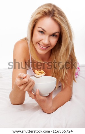 blonde woman having healthy  breakfast on her bed , - stock photo