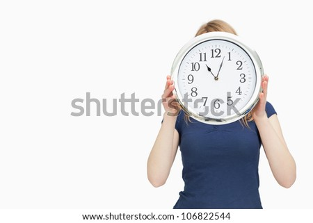 Blonde woman holding a clock against a white background - stock photo