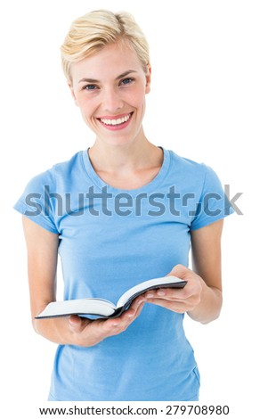 Blonde woman holding bible and looking at camera on white background - stock photo