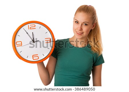 Blonde woman holding big clock in hand smiling because it is five minutes to lunchtime, isolated over white.