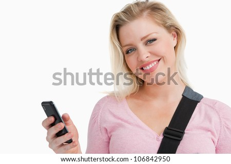 Blonde woman holding her mobile phone while writing a text against a white background - stock photo
