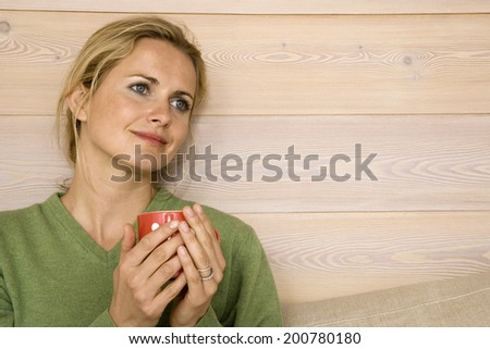 Blonde woman holding mug daydreaming leaning head against wall close up - stock photo