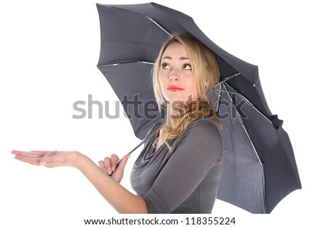 Blonde woman holding umbrella looking up checking for water on white background - stock photo