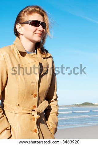 Blonde woman in a leather coat and sunglasses smiling. Blue sky in the background.