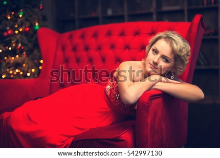 Blonde woman in a red evening dress lying on a red couch on a background of the Christmas tree