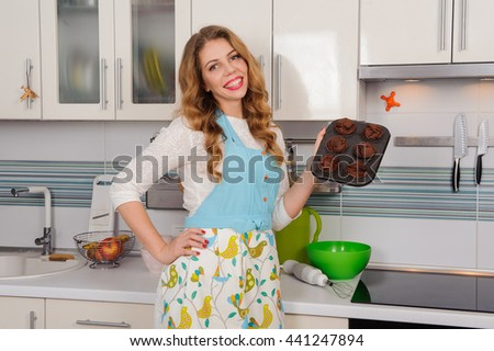 blonde woman in apron with cupcakes in kitchen