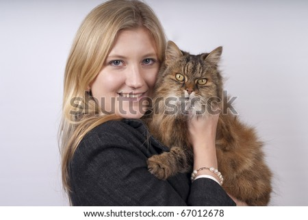 Blonde woman in black jacket holding brown tabby cat - stock photo