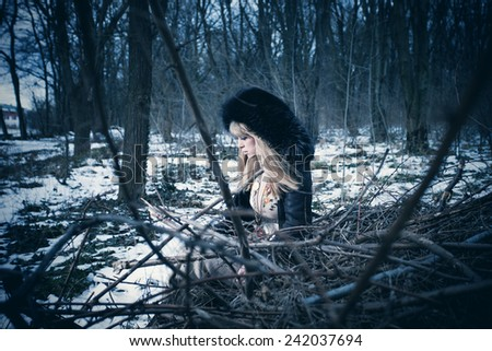 blonde woman in coat with fur hood sit on branches in the forest, cold winter day