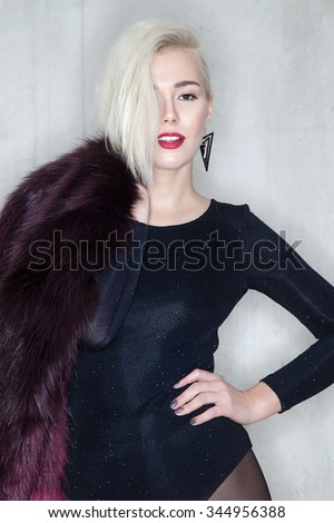 Blonde woman in colorful coat with short hair - stock photo