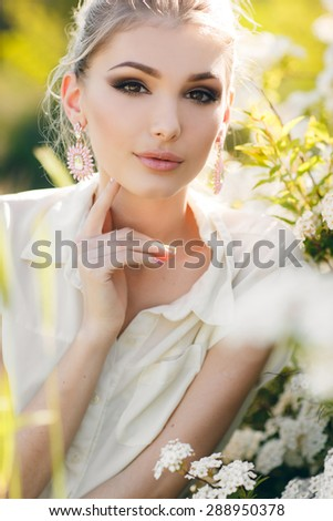 Blonde woman in flowers. beautiful happy blonde woman in the park on a warm summer day - stock photo
